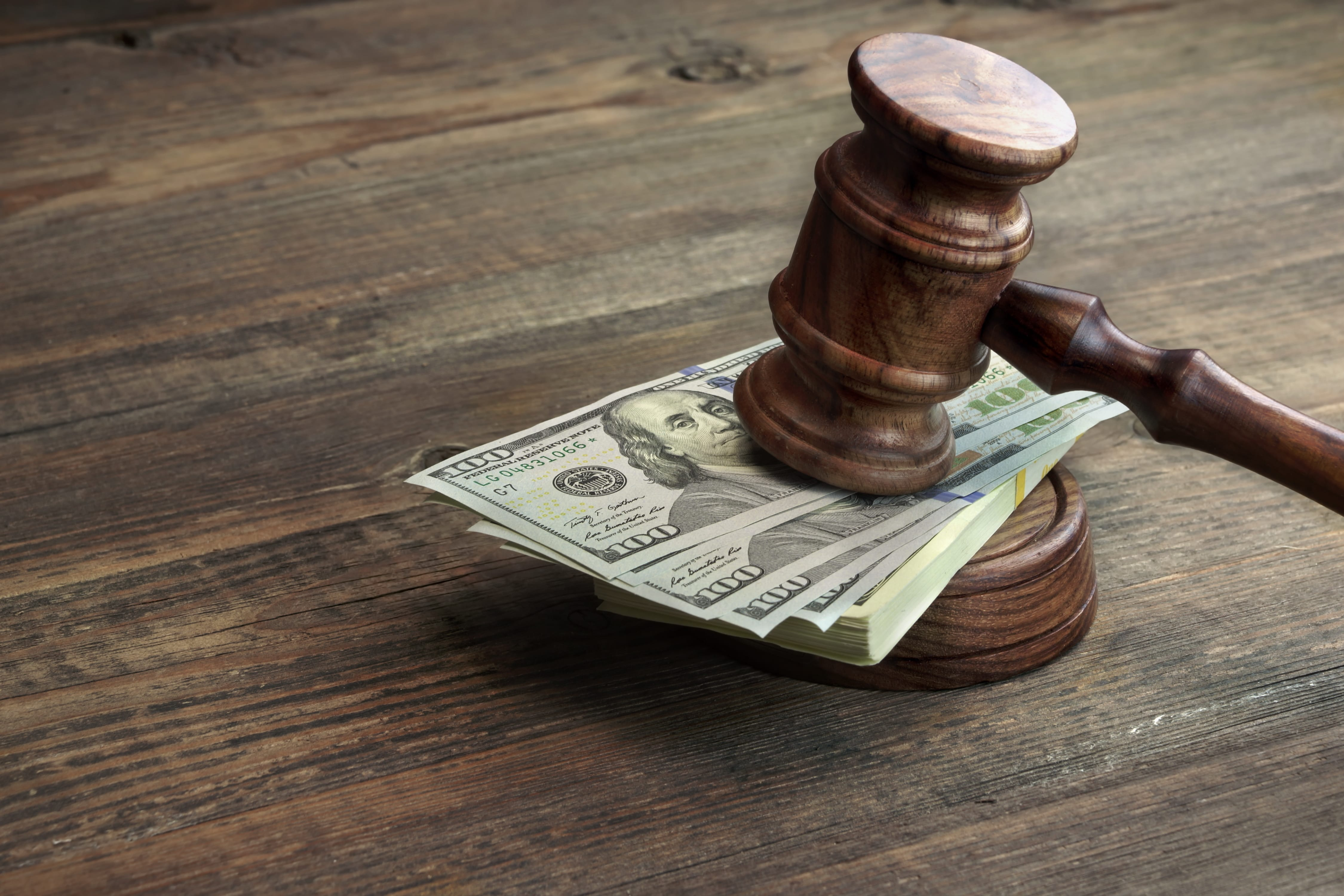 gavel sits on a pile of bills, pending the financial outcome of a divorce